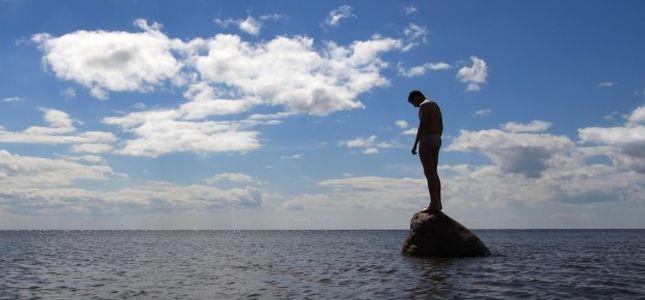 Individu isolé sur un rocher immergé