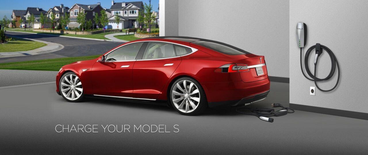 Une automobile Tesla S prêt de sa station de chargement à domicile
